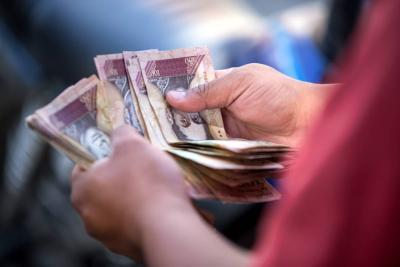 Venezolanos sobreviven vendiendo billetes de 100 bolívares en buses de Bogotá