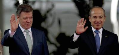El presidente colombiano Juan Manuel Santos en compañía de su homólogo mexicano Felipe Calderón saludan en la ceremonia desde el palacio presidencial de México, Los Pinos.