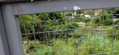 Los residentes de la invasión  arrancaron el sello colocado por la Administración en esta puerta metálica que da a la autopista.