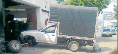 Denuncian que taller de mécanica repara carros sobre el andén