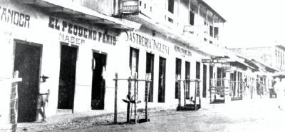 La fotografía capta una parte de la Avenida Santander en 1931. Los nombres de los negocios reflejaban la influencia extranjera en el recién creado municipio de Barrancabermeja, en un sector cercano al muelle.