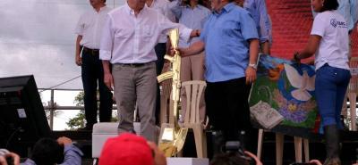 El presidente de Colombia, Juan Manuel Santos ,con el máximo líder de las Farc, Rodrigo Londoño, alias 'Timochenko', durante la ceremonia de dejación de armas ayer en Mesetas, Meta.