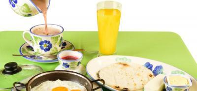 Huevos fritos, jugo natural y arepa.