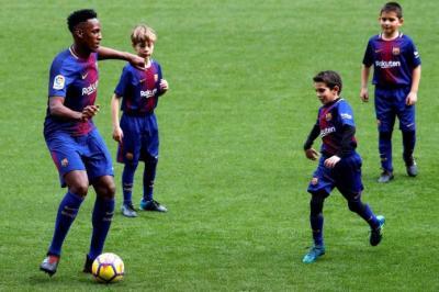 El central colombiano Yerry Mina juega un rondo con niños del equipo alevín durante su presentación como nuevo jugador del FC Barcelona que se celebró ayer en el Camp Nou.