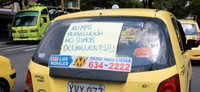 """Con pancartas en sus carros, los taxistas les solicitan a las autoridades que """"no los persigan más""""."""