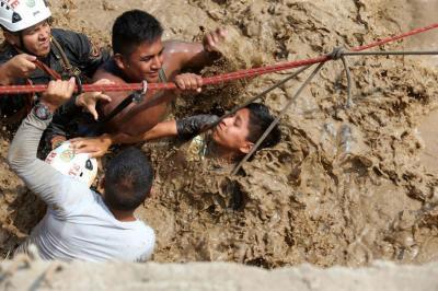 Personal de la policía nacional del Perú rescata a personas atrapadas por las inundaciones producidas por el desborde de los ríos Rímac y Huaycoloro en el sector denominado Carapongo al este de la ciudad de Lima.